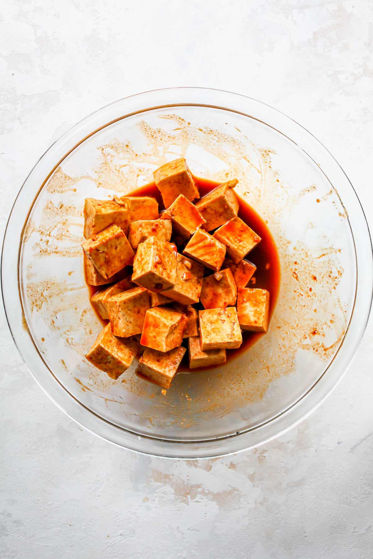 Cubes of tofu marinating in a large mixing bowl