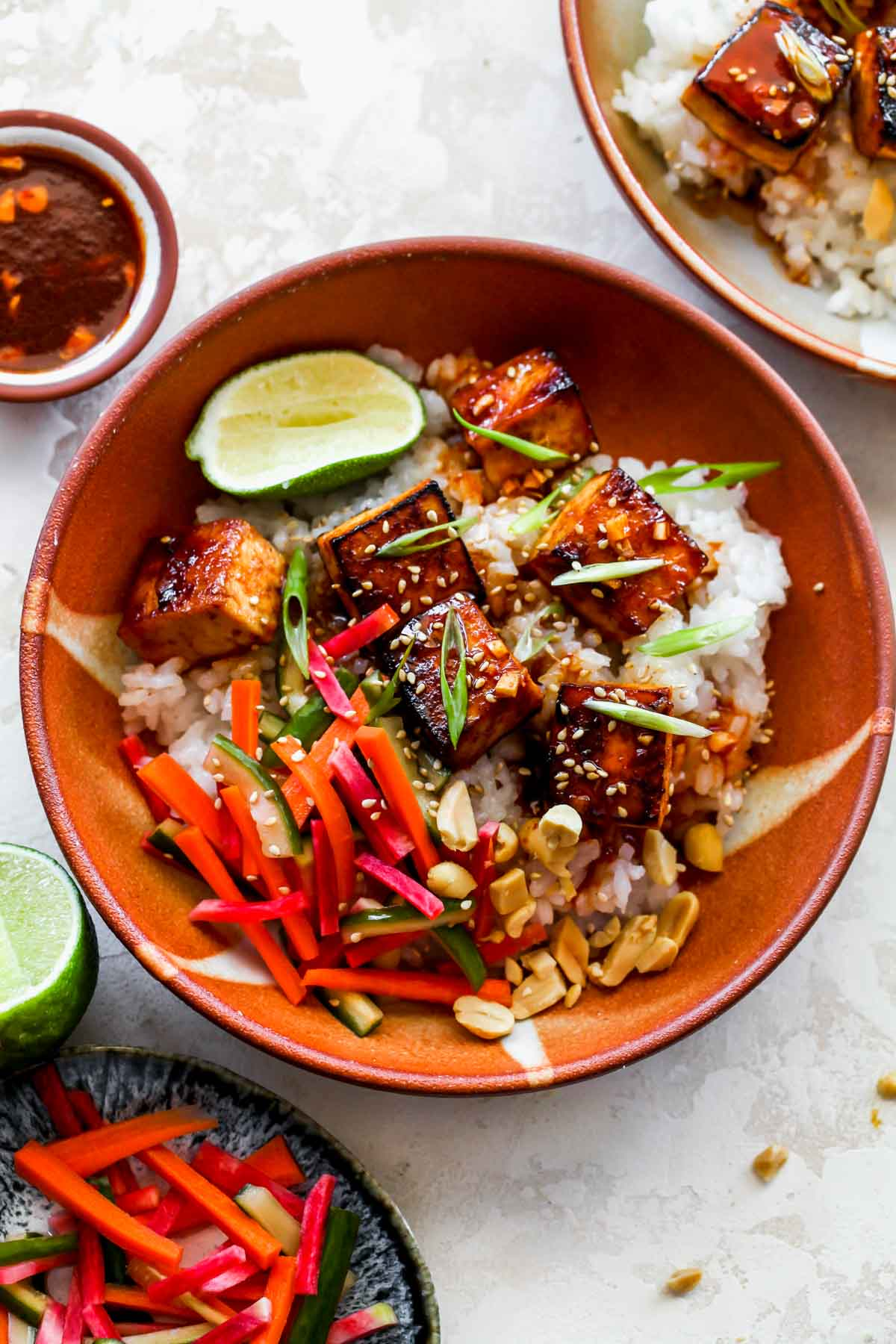 Gochujang marinated tofu and rice in a bowl topped with pickled veggies