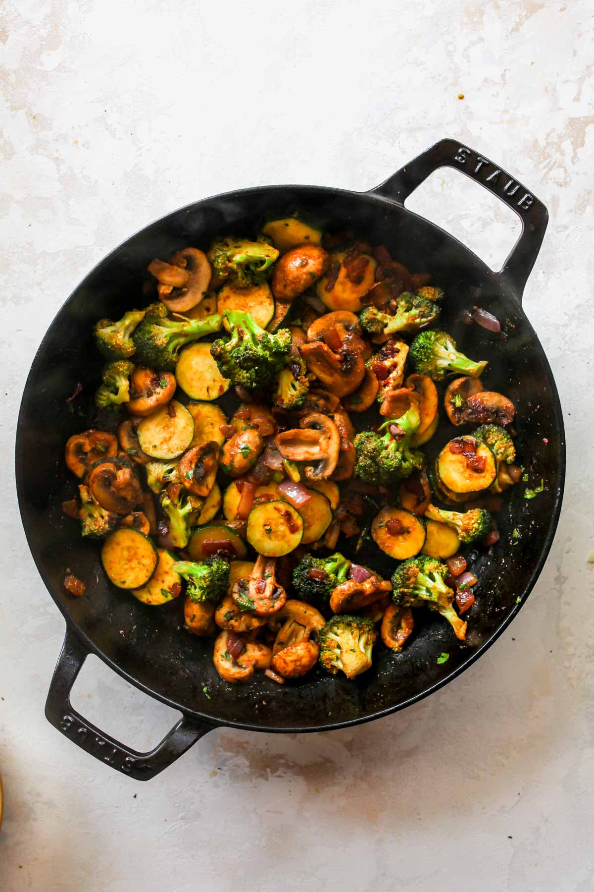 Mushrooms, broccoli, zucchini, and red onion sautéing in a skillet