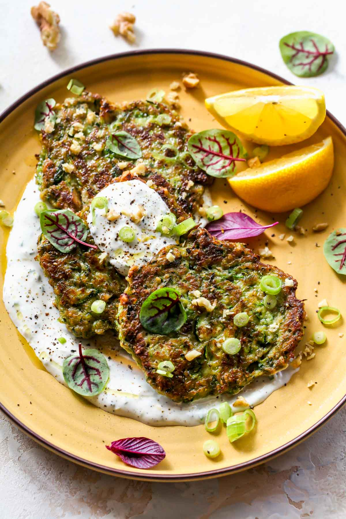 Zucchini fritters arranged on a plate with garlic sauce and lemons