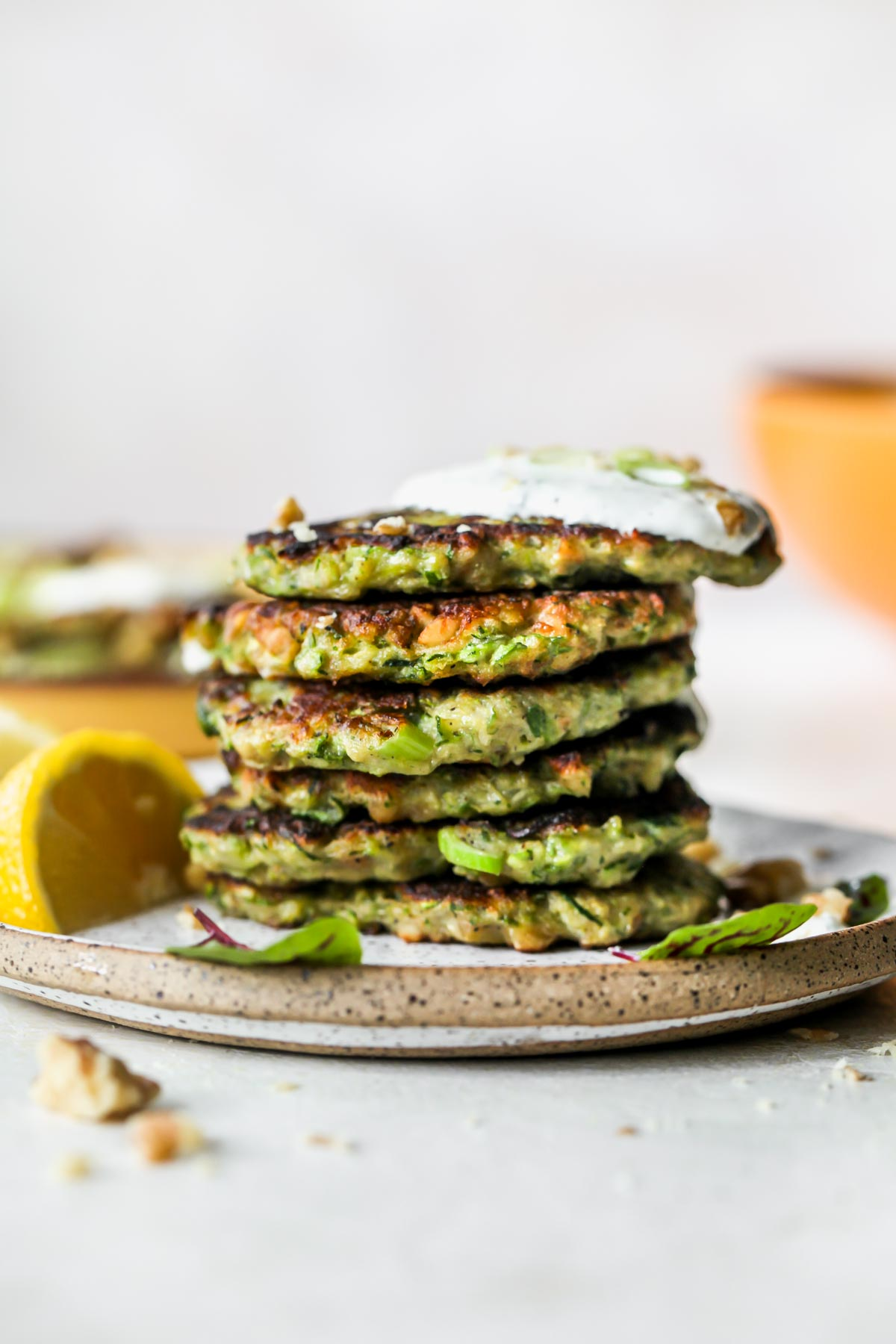 A stack of zucchini fritters on a plate topped with garlic sauce