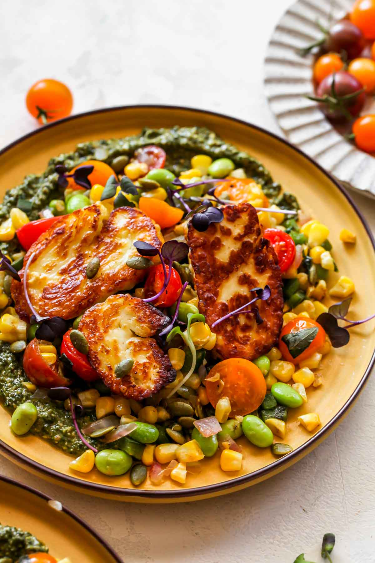 Succotash and halloumi styled on a yellow plate with pesto