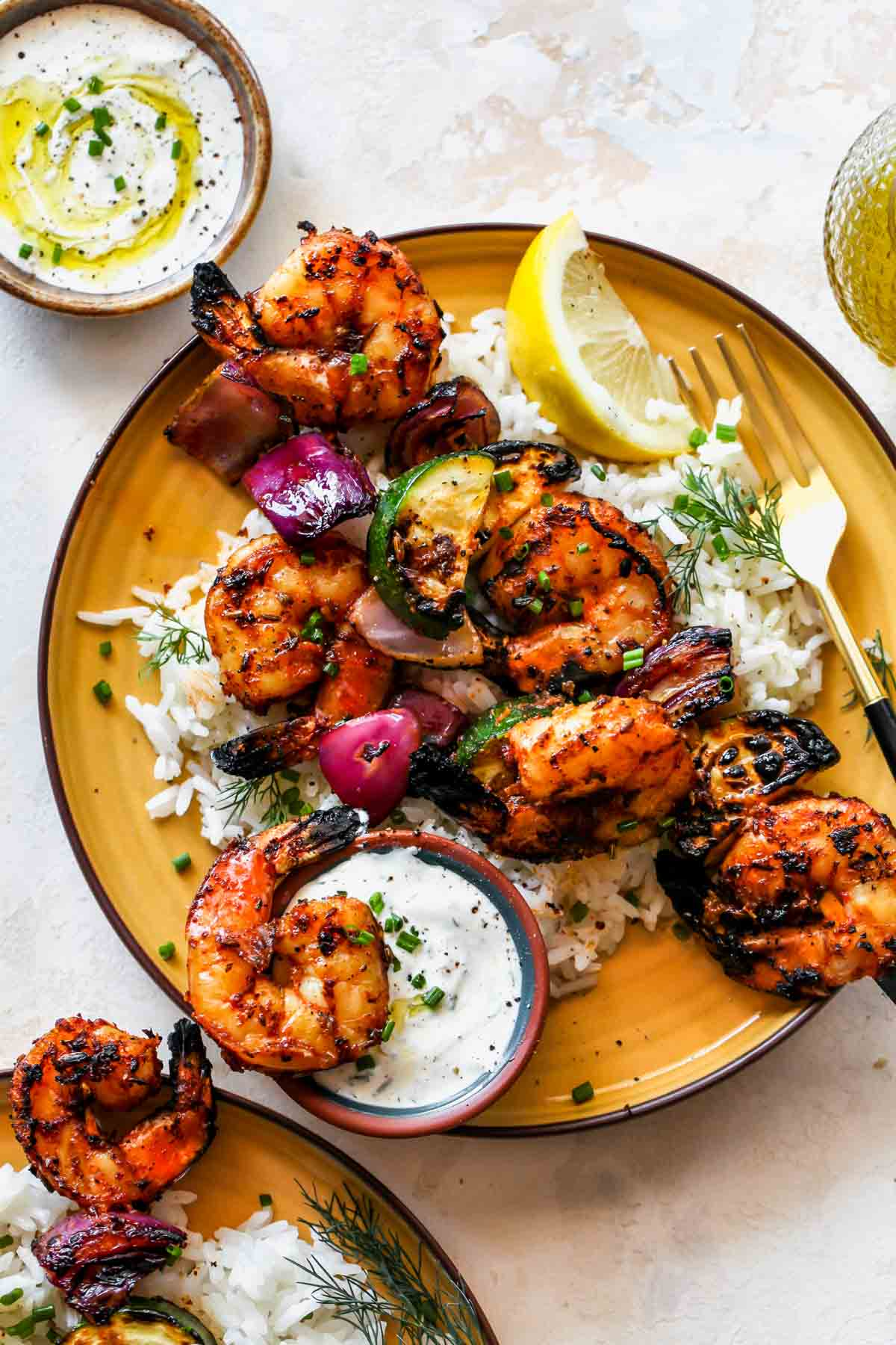 Shrimp kebabs on a bed of rice with a side of creamy sauce