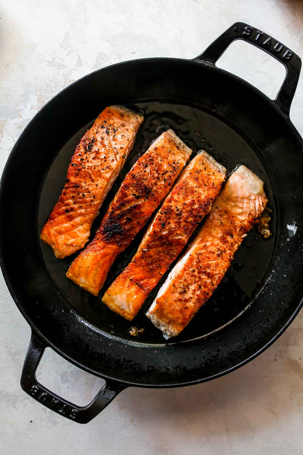 Four salmon fillets being seared in a cast iron skillet