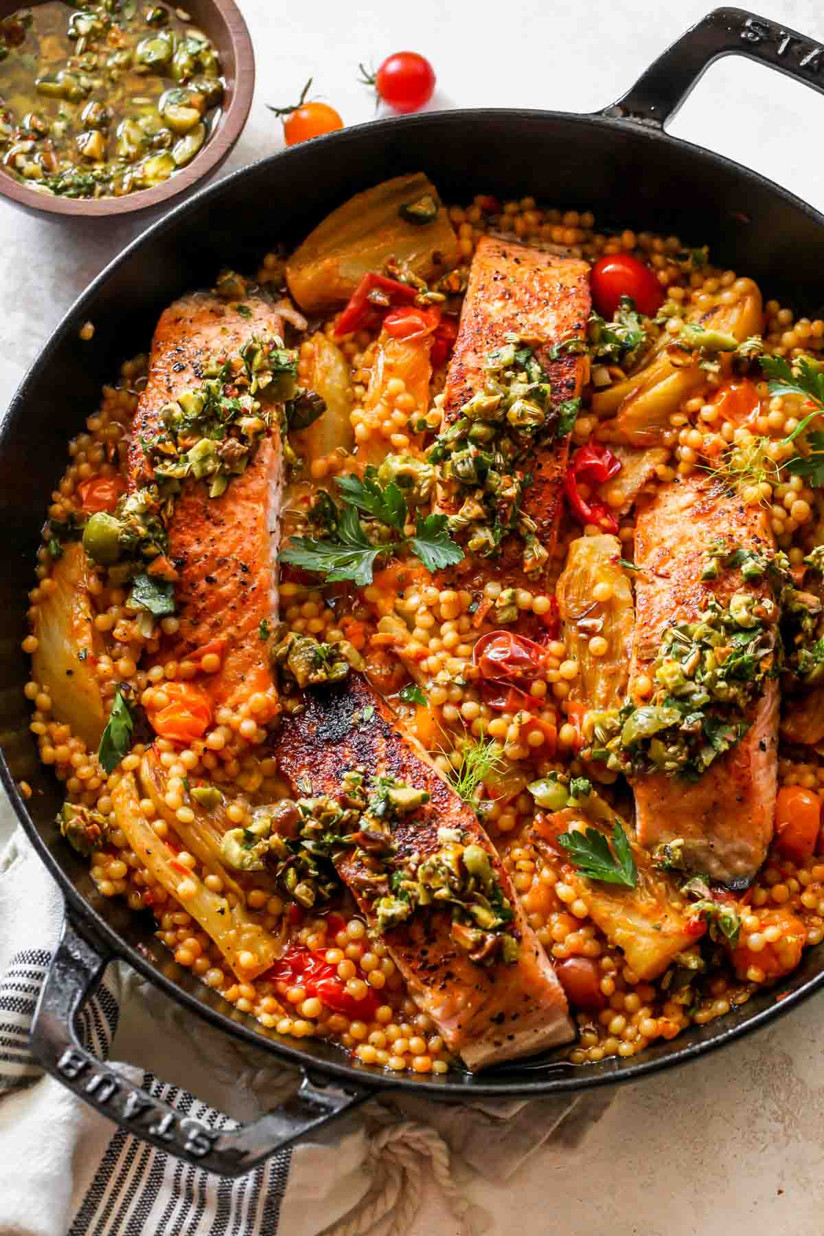 Salmon over couscous in a skillet topped with olive salsa