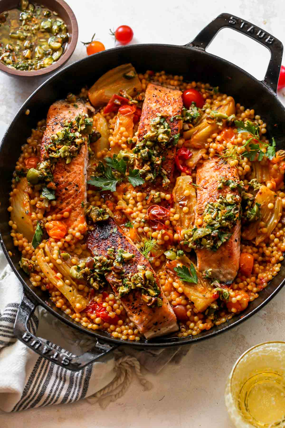 Salmon being added to a skillet of couscous, tomatoes, and fennel