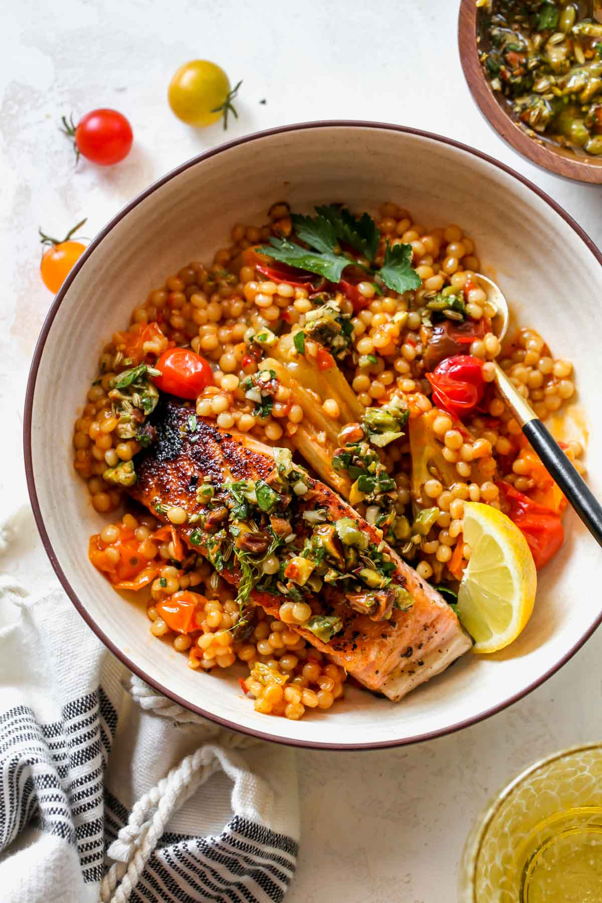 A tan bowl filled with couscous, salmon, olive salsa, and lemon