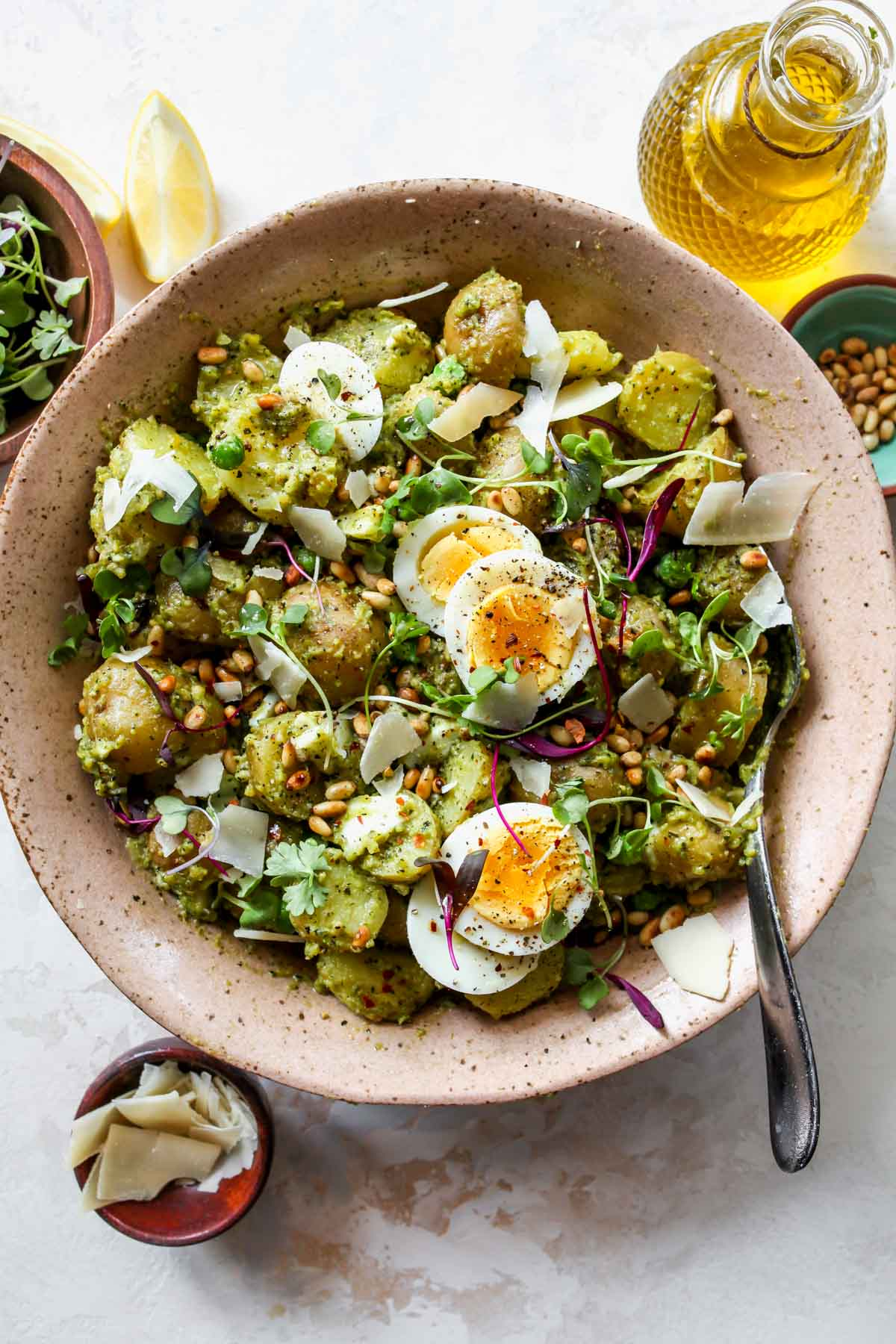 Pesto potato salad styled in a pink bowl