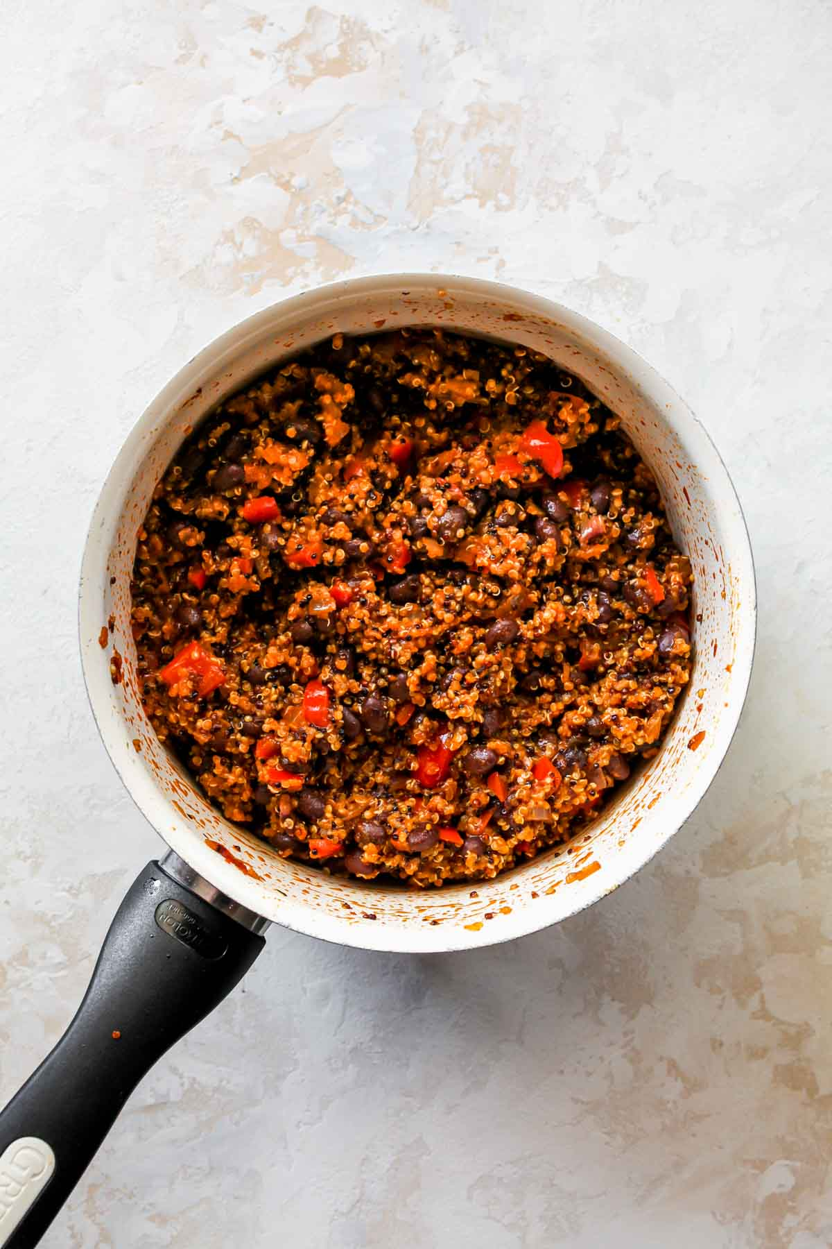 Black beans being stirred into a saucepan filled with quinoa