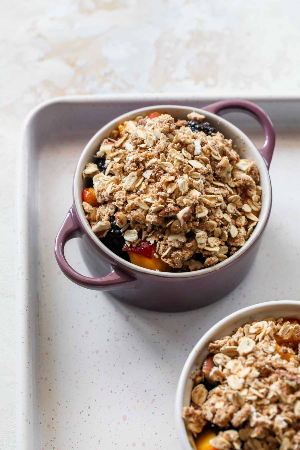 A mini ramekin filled with fruit mixture and oat topping