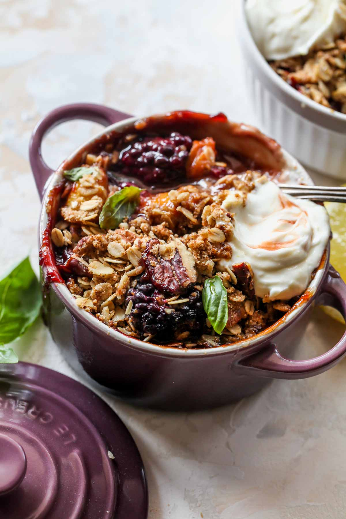 Peach and blackberry crisp topped with oat crumble and whipped goat cheese