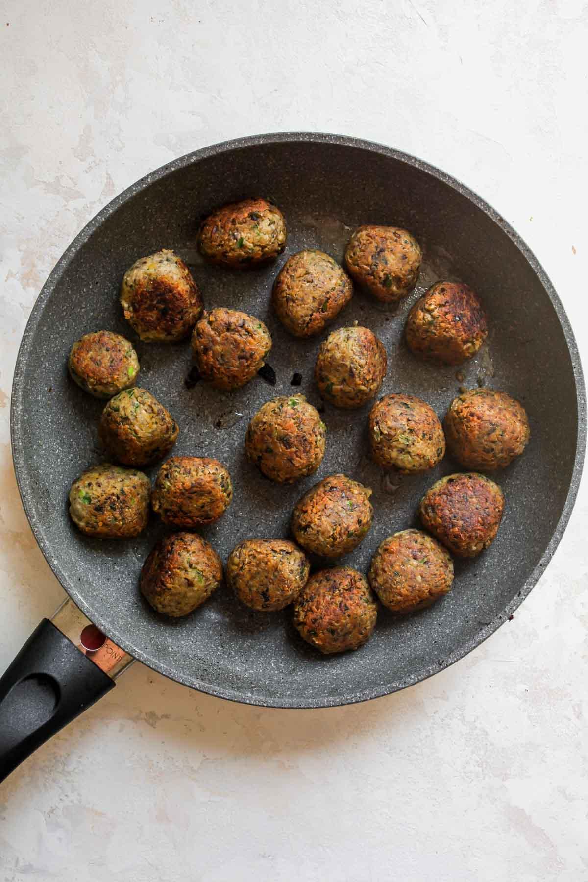 Mushroom meatballs being sautéed in a skillet