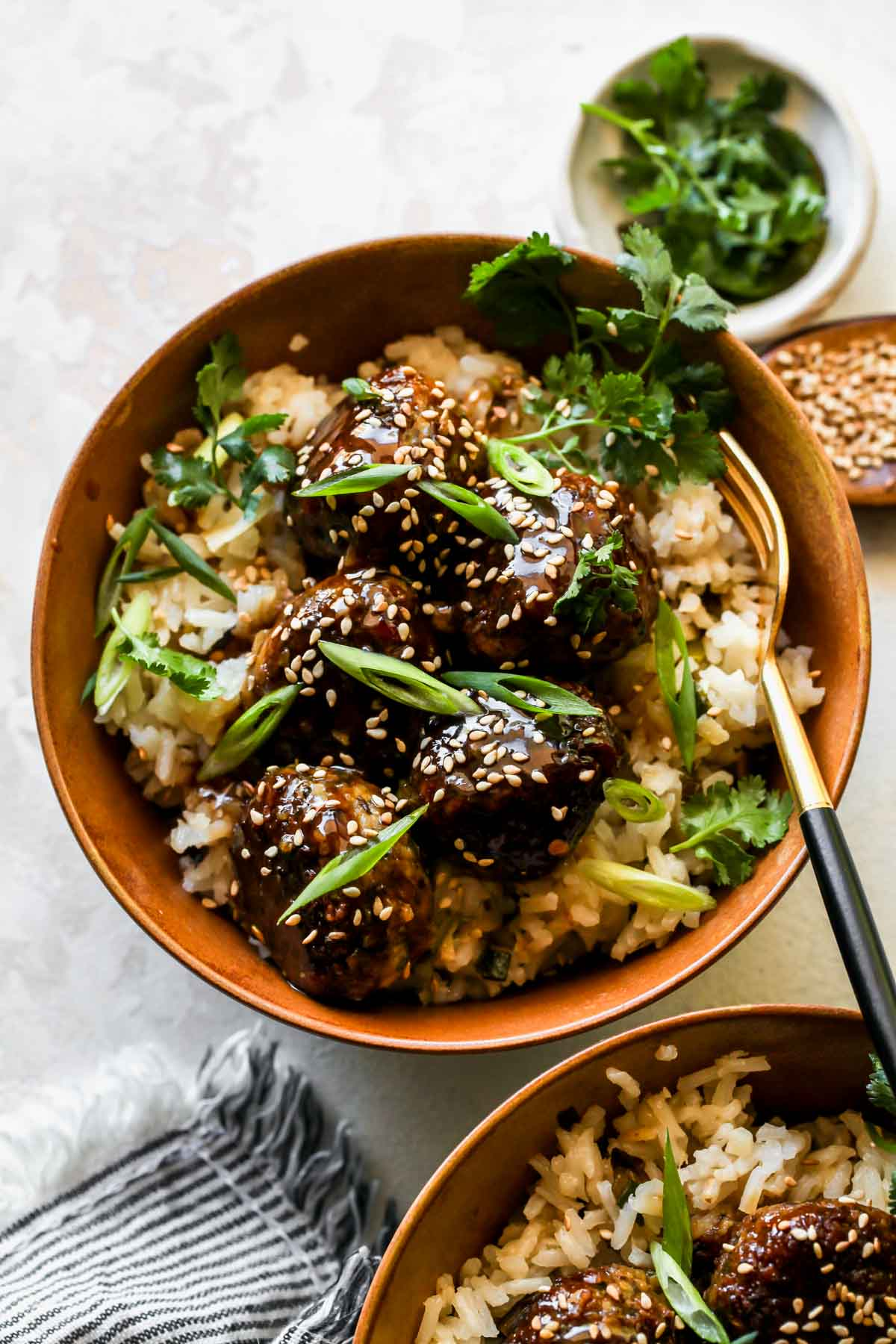 Mushroom meatballs over white rice in a gold bowl topped with scallions