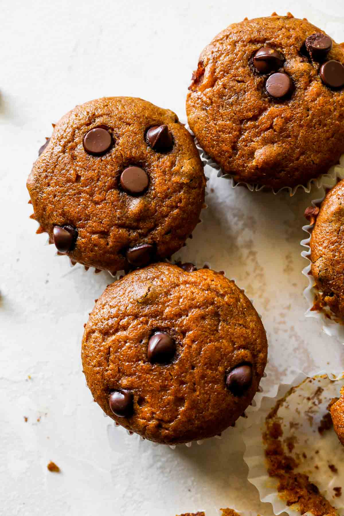 Four Pumpkin Chocolate Chip Muffins lined up next to eachother