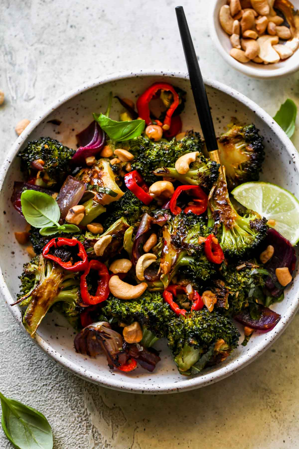 Chili-garlic roasted broccoli topped with cashews and lime in a serving dish