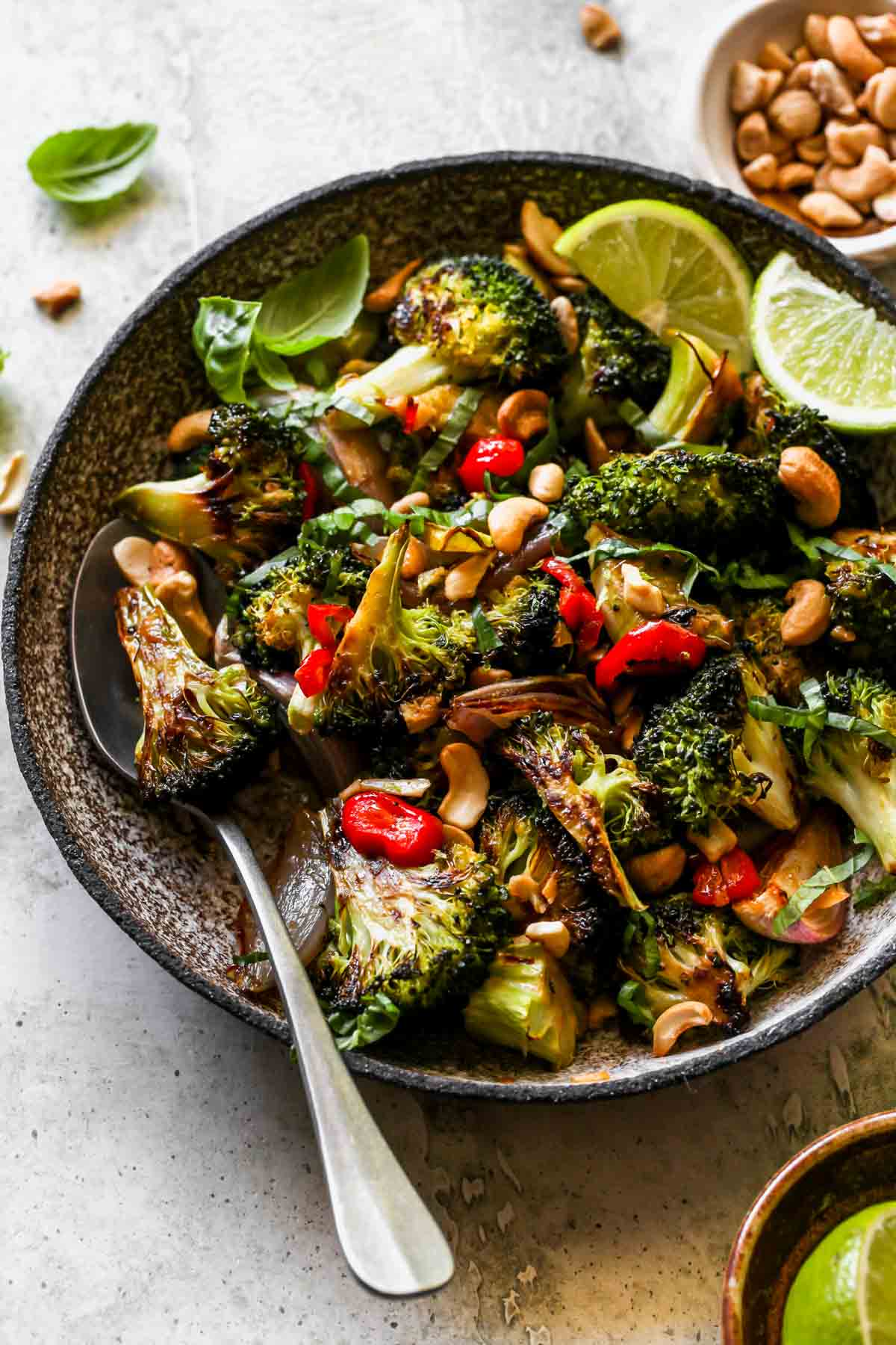 Roasted broccoli with a serving spoon in a gray bowl
