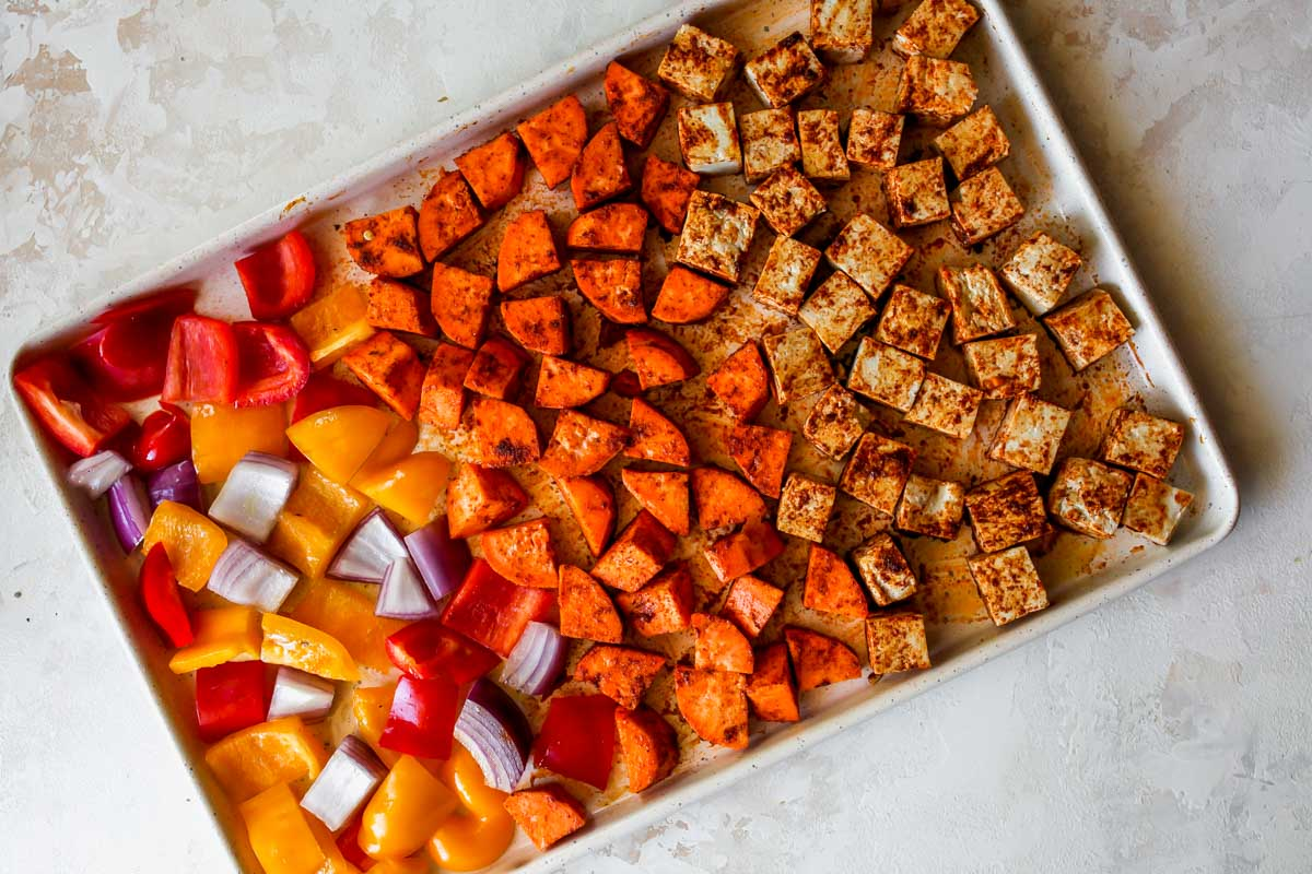 Tofu, sweet potatoes, peppers, and onions arranged on a sheet pan
