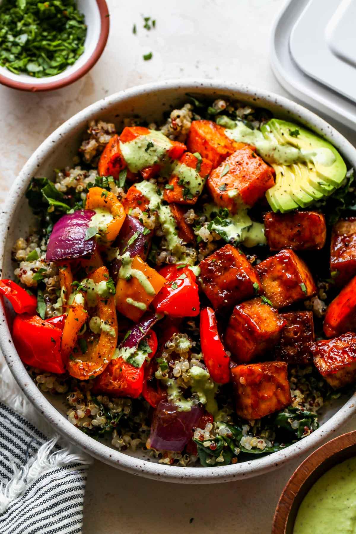 Sheet pan tofu bowls filled with quinoa, kale, roasted veggies, and green sauce