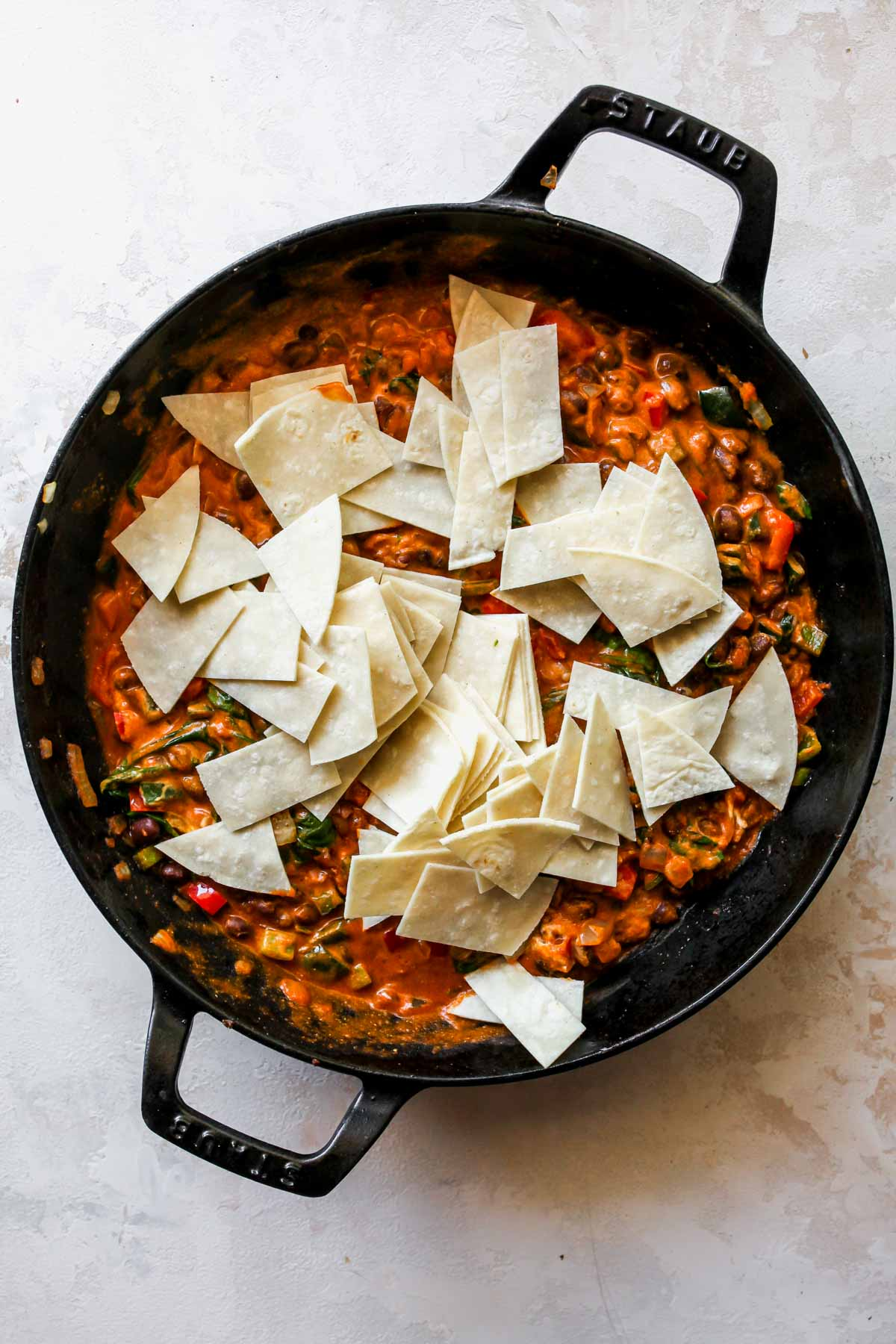 Chopped tortilla strips being stirred in a pan of enchilada sauce