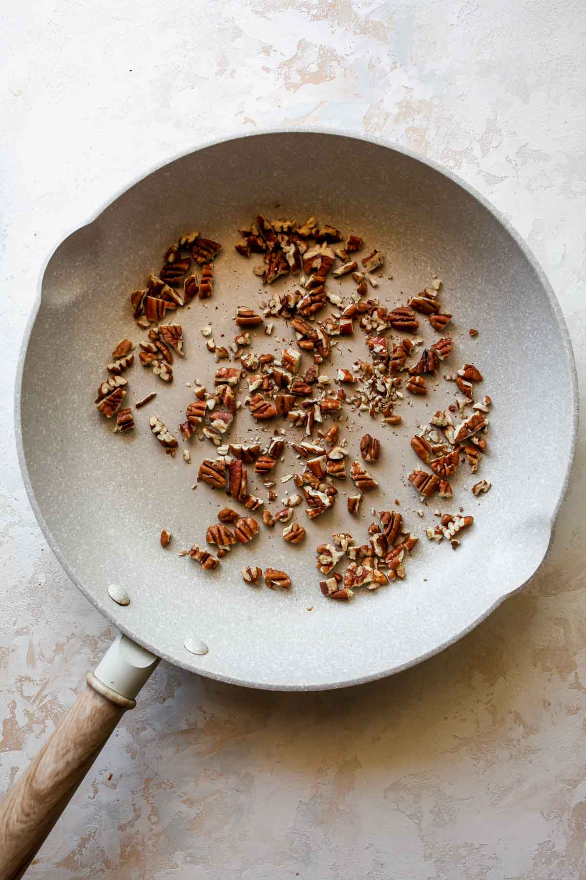 Chopped pecans toasting in a skillet