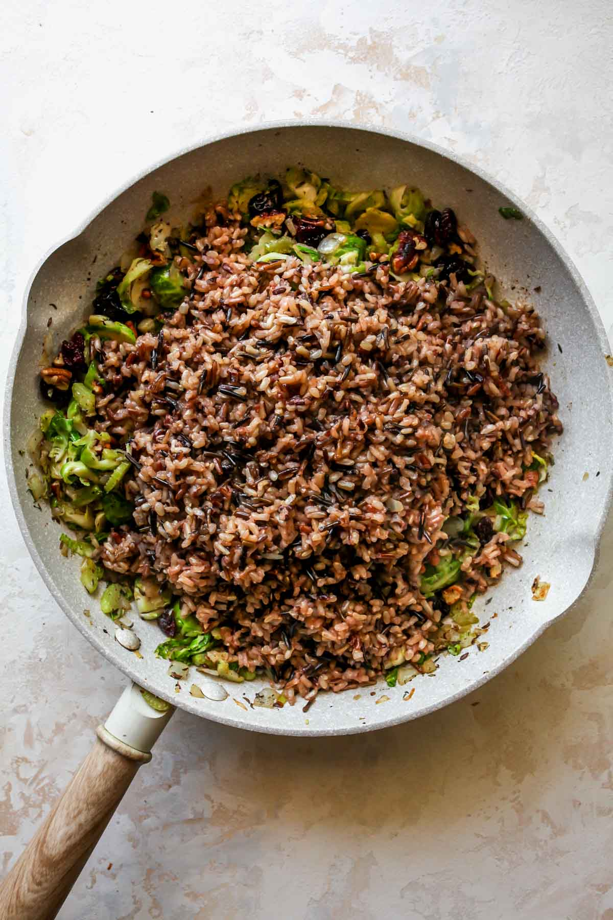 Cooked wild rice being added to a skillet of veggies