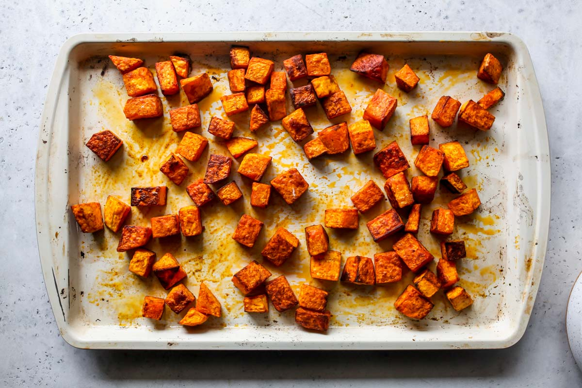Cubes of butternut squash on a baking sheet after being roasted
