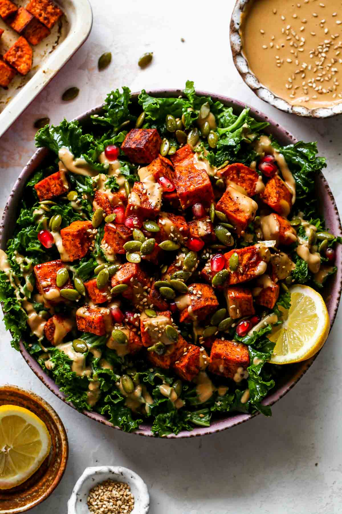 Kale salad topped with roasted sweet potatoes, pomegranate, and almond butter dressing