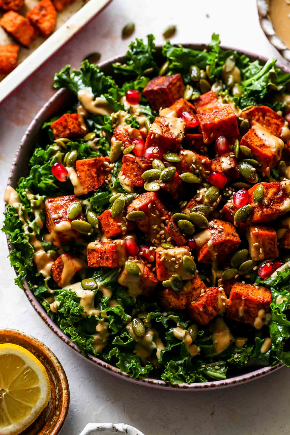 Kale and sweet potato salad on a platter topped with pomegranate and pumpkin seeds